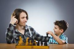 Zwei Jungen oder Brüder, die das Schach lokalisiert auf grauem Hintergrund spielen lizenzfreies stockbild
