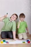 Zwei Jungen sitzen auf Fußboden und zeigen ihre Zeigefinger Stockbilder