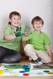 Zwei Jungen sitzen mit erfüllten Gesichtern und zeigen Palmen Lizenzfreie Stockfotografie