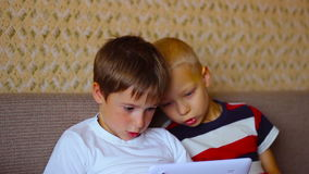 Zwei Jungen spielen auf einer weißen Platte, die auf sitzt stock footage