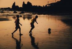 Zwei Jungen spielen Fußball auf Strand in der Dämmerung, Goa, Indien lizenzfreie stockbilder
