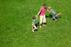 Zwei Jungen spielen mit dem Erwachsenen einen Rasen. Die Draufsicht. Stockfotos