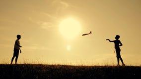 Zwei Jungen spielen mit einer h?lzernen Fl?che bei Sonnenuntergang Schattenbild von den Kindern, die mit einem Flugzeug spielen T stock video