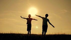 Zwei Jungen spielen mit einer h?lzernen Fl?che bei Sonnenuntergang Schattenbild von den Kindern, die mit einem Flugzeug spielen T stock footage