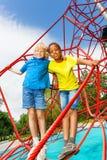 Zwei Jungen stehen, umarmend auf roten Seilen des Netzes Stockfotografie