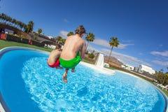 Zwei Jungen stellen eine Kanonenkugel in das Pool her Lizenzfreie Stockfotografie