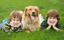 Zwei Jungen und ein Hund Stockfotos