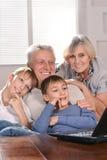 Zwei Jungen und Großeltern mit einem Laptop lizenzfreie stockfotografie