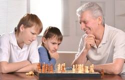Zwei Jungen und Großvater, die Schach spielen lizenzfreies stockfoto