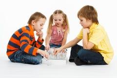 Zwei Jungen und hübsches Mädchen, die Schach spielen stockbilder