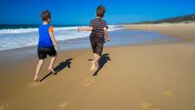 Zwei Jungen und Hund, die in Wasser auf dem Strand laufen und spritzen