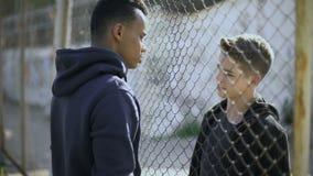 Zwei Jungen von verschiedenen Nationalitäten sprechend, reich und Armen trennten sich durch Zaun stock video footage