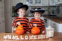 Zwei Jungen zu Hause, Kürbise für Halloween zubereitend Stockbilder