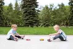Zwei Jungenkinder, die draußen zusammen mit Spielwaren spielen Stockfotografie