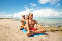 Zwei junger Mann und Frau auf dem Strand, der Eignungsyoga tut, trainieren zusammen Acroyoga-Element für Stärke und Balance stockbild