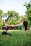 Zwei junges kaukasisches Frauenjogi, das Balancenrückseitenausdehnung acro Yoga tut, wirft auf Frauen, die Training im Park am su Lizenzfreie Stockbilder