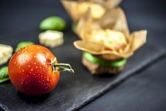 Zwei Käsemuffins, -basilikum, -tomate und -käse lizenzfreie stockfotos