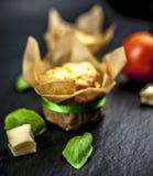 Zwei Käsemuffins, -basilikum, -tomate und -käse stockfotografie