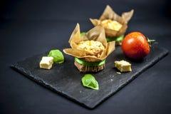 Zwei Käsemuffins, -basilikum, -tomate und -käse lizenzfreie stockbilder