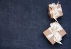 Zwei Kästen in eco Papier auf dem darck Blauholztisch Beschneidungspfad eingeschlossen Pakete oder Geschenke gebunden mit Satinwe Lizenzfreie Stockfotografie