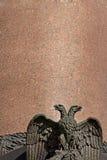 Zwei-köpfige Adlerskulptur auf einem Granithintergrund der Alexander-Spalte auf Palast-Quadrat in Petersburg Lizenzfreie Stockbilder