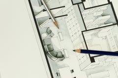 Zwei künstlerische Zeichnungsbleistifte stellten auf architektonische isometrische Zeichnung des tatsächlichen Immobiliengrundris Stockbilder