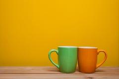 Zwei Kaffeetassen auf Holztisch Stockfotos