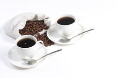 Zwei Kaffeetassen mit Kaffeebohnen Stockbild