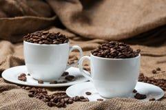 Zwei Kaffeetassen mit Kaffeebohnen Stockfoto