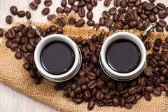 Zwei Kaffeetassen mit Kaffeebohnen lizenzfreie stockfotografie