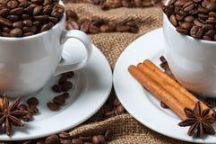 Zwei Kaffeetassen mit Kaffeebohnen, Anissamen und Zimt Stockfotografie