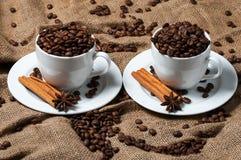 Zwei Kaffeetassen mit Kaffeebohnen, Anissamen und Zimt Stockfotos