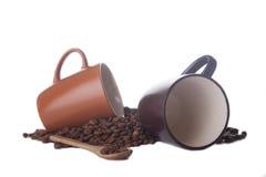 Zwei Kaffeetassen und Kaffeebohnen auf Weiß Lizenzfreie Stockfotos