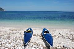 Zwei Kajaks, die auf dem Strand liegen Stockfotografie