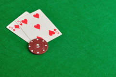Zwei Karten mit einem Pokerchip mit dem Wert von fünf stockfotografie