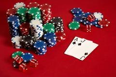 Zwei Karten und Chips auf einem roten Hintergrund Große Wette des Spielgeldes Karten - Ace und Jack Ihre Verteilung am Tisch Lizenzfreie Stockfotos
