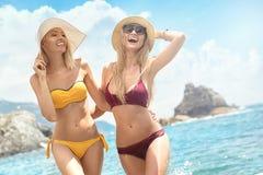 Zwei kaukasische Frauen, die Spaß auf dem Strand haben Stockbild