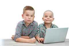 Zwei kaukasische Jungen, Brüder auf einem weißen lokalisierten Hintergrund man unterrichtet den anderen, um einen Laptop zu benut lizenzfreie stockbilder
