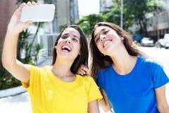 Zwei kaukasische Mädchen, die selfie mit Mobiltelefon nehmen Lizenzfreies Stockbild