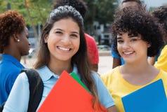 Zwei kaukasische Studentinnen mit Gruppe multiethnischen Studenten Stockfotos