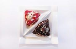Zwei Kekse mit einer Füllung von Beeren und von Creme, auf einer weißen Platte und besprüht mit weißer und dunkler Schokolade Stockfotografie