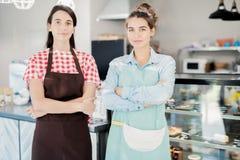 Zwei Kellnerinnen, die im Café aufwerfen stockbild
