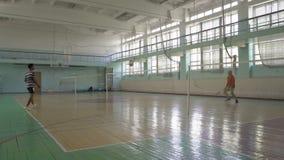Zwei Kerl-Spiel-Badminton-in der Schule Sporthalle