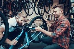 Zwei Kerle überprüfen Fahrrad in der Sport-Werkstatt stockbild