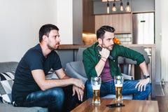 Zwei Kerle, die aufpassenden Fußball des Bieres trinken stockbilder