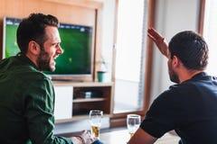 Zwei Kerle, die aufpassenden Fußball des Bieres trinken stockfotografie