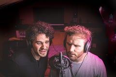 Zwei Kerle, die in einem Musikstudio singen lizenzfreie stockbilder