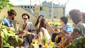 Zwei Kerle, die Gitarre und Saxophon, Mädchen macht Fotos von glücklichen Freunden spielen stock video