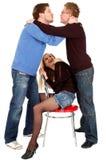 Zwei Kerle, die vor einem hübschen Mädchen des Sitzens küssen Lizenzfreies Stockbild