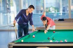 Zwei Kerle im Poolbillard schlagen das Spielen von Poolbillard mit einer Keule Stockfotografie